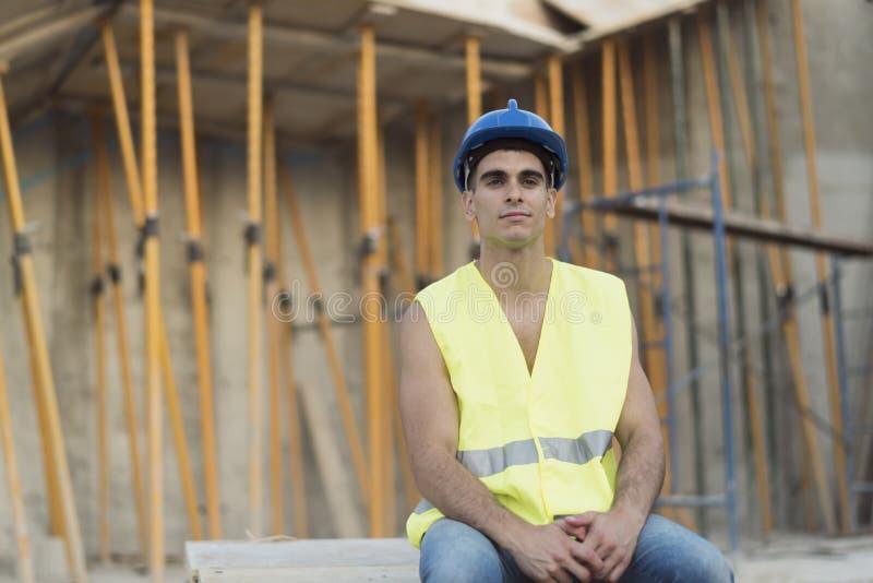 Giovane lavoratore di costruzioni che ha un resto nel cantiere fotografia stock