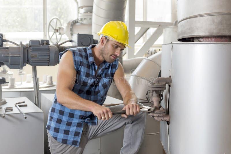 Giovane lavoratore manuale che per mezzo della chiave sulla macchina di industriale immagine stock