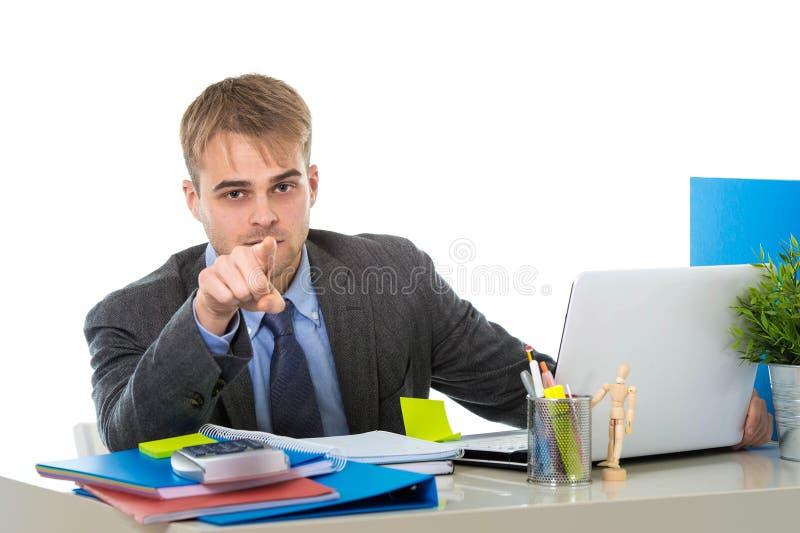 Giovane lavoro attraente dell'uomo d'affari occupato con il computer portatile all'ufficio che indica con il suo dito fotografia stock libera da diritti