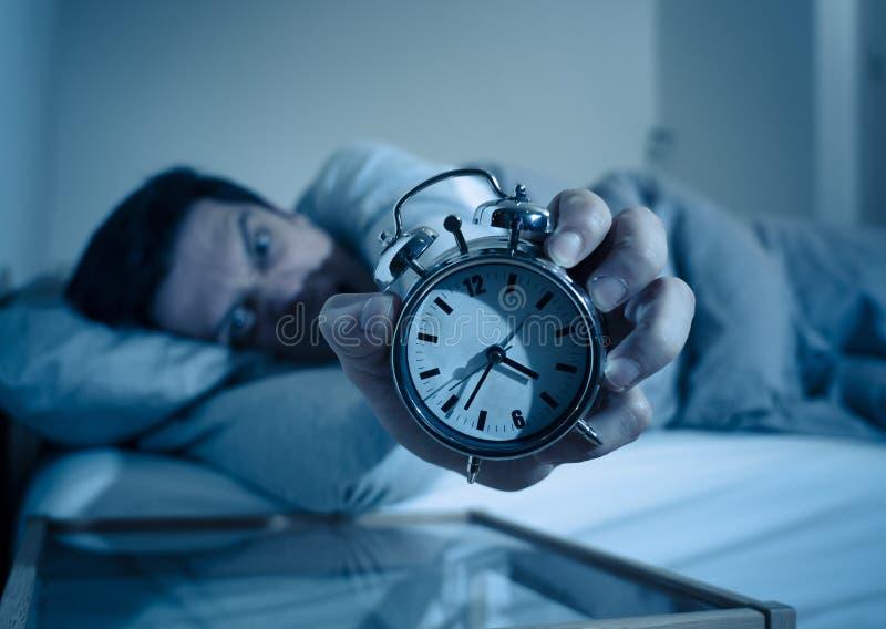 Giovane a letto con la sensibilità della sveglia disperata e l'emergenza non capace di dormire con insonnia fotografia stock libera da diritti