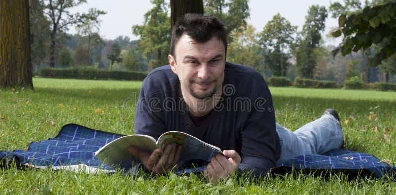 Giovane lettura adulta alla sosta immagini stock