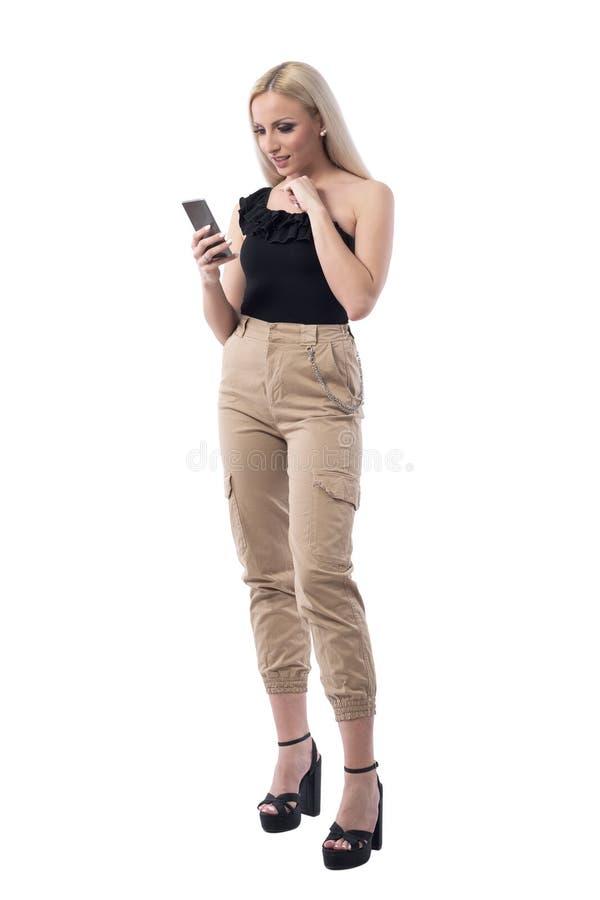 Giovane lettura bionda incerta confusa della donna ed usando media sociali dello Smart Phone immagini stock