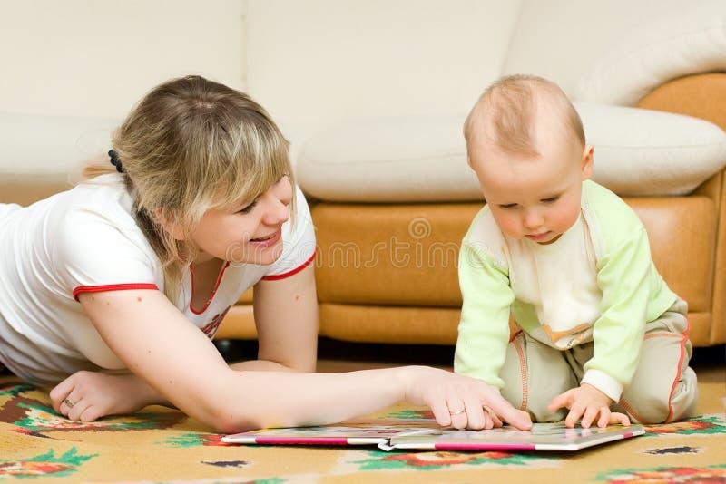 Giovane lettura della mamma il suo piccolo libro del figlio su un pavimento fotografia stock libera da diritti
