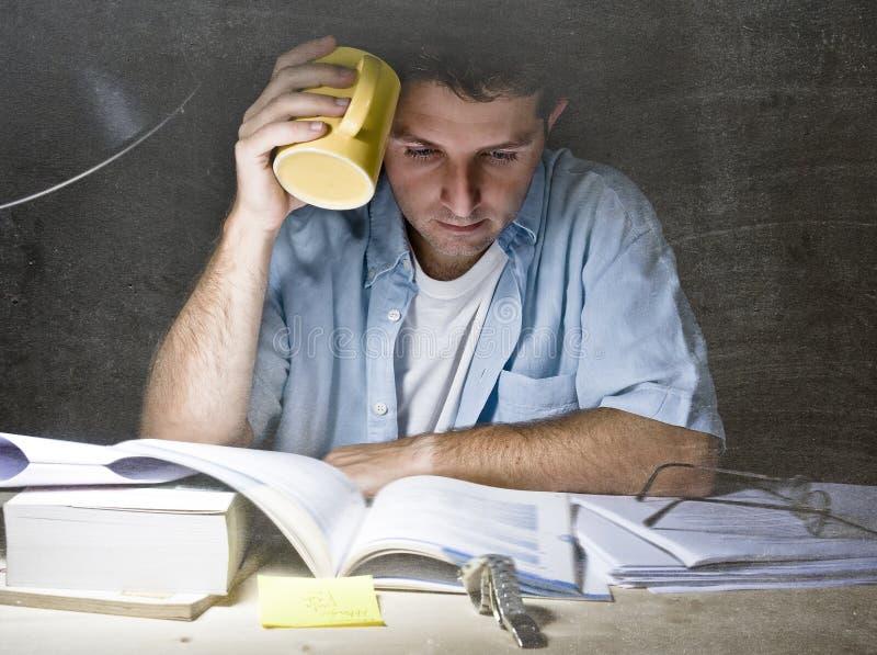Giovane lettura dello scrittorio dello studente a casa che studia alla notte con il mucchio dei libri e del caffè immagini stock libere da diritti