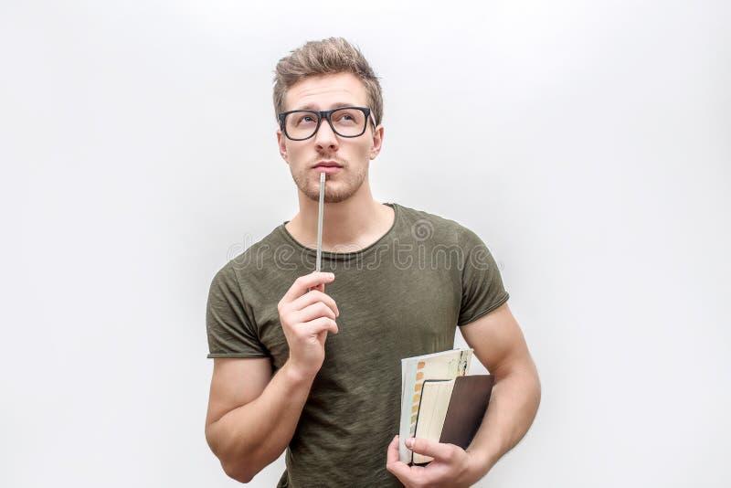 Giovane in libri e matita verdi della tenuta della camicia in mani Considera la macchina fotografica attraverso i vetri Isolato s fotografia stock libera da diritti