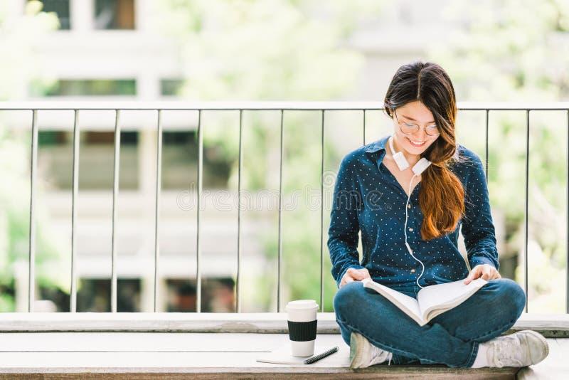 Giovane libro di lettura asiatico della ragazza dello studente di college per esame, seduta al campus universitario con lo spazio fotografia stock libera da diritti