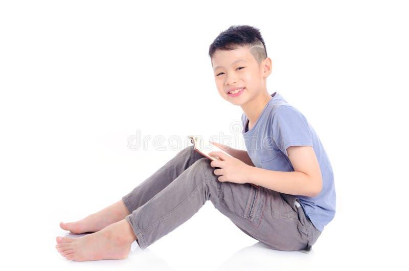 Giovane libro di lettura del ragazzo sopra bianco fotografia stock