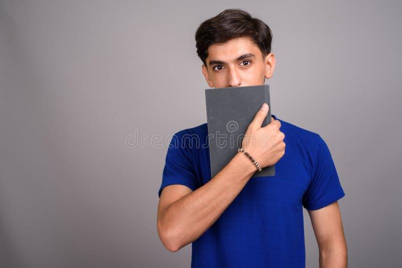 Giovane libro persiano bello della tenuta dello studente dell'adolescente fotografie stock