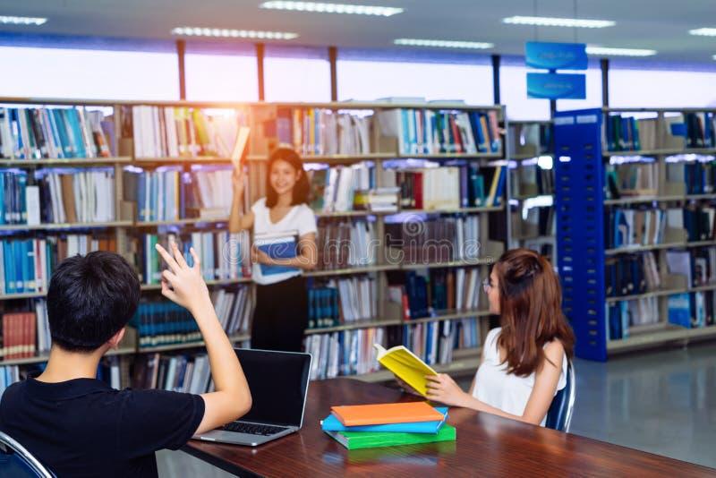 Giovane libro scelto asiatico del gruppo di studenti con l'amico fotografia stock