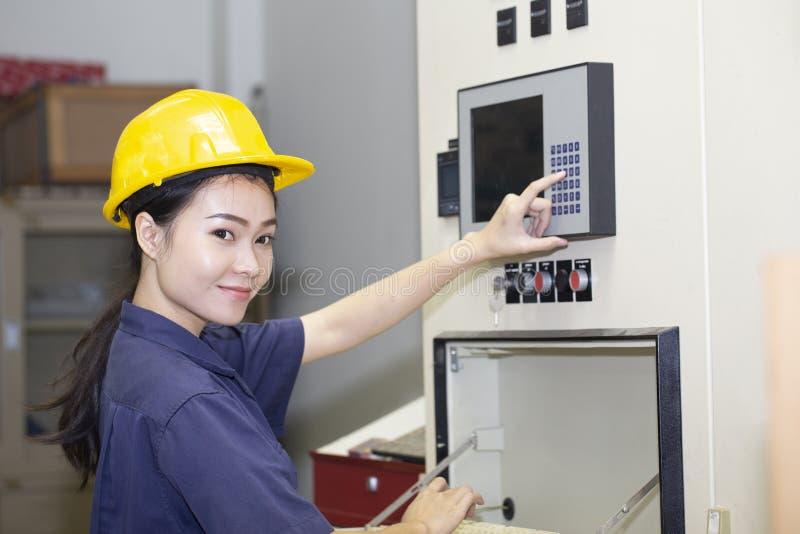 Giovane macchina asiatica di messa a punto e di prova dell'ingegnere della donna fotografia stock libera da diritti