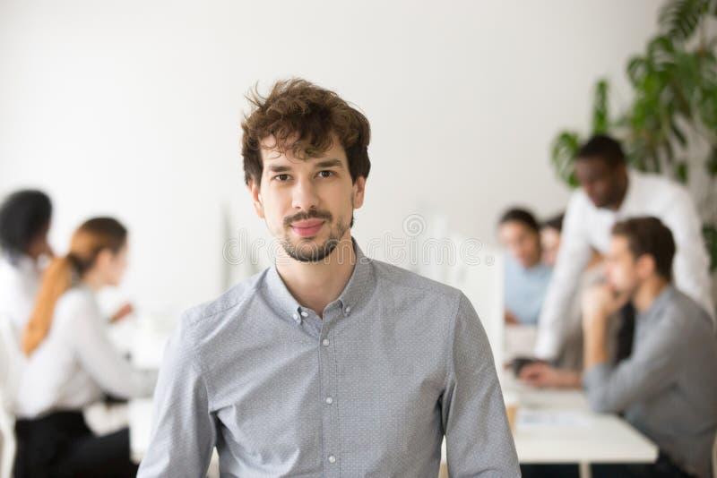 In giovane macchina fotografica di sguardo professionale esperta che posa nell'ufficio, p immagini stock