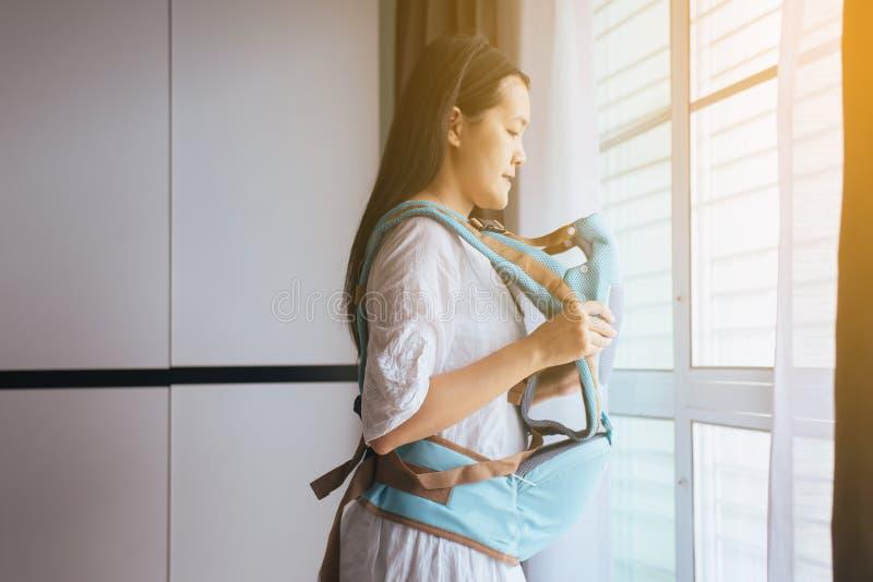 Giovane madre asiatica con un marsupio a casa immagini stock libere da diritti