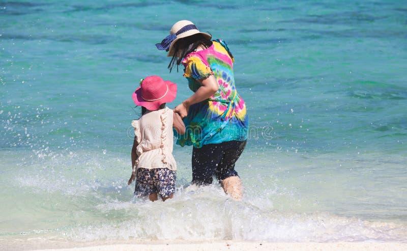 Giovane madre asiatica e figlia sveglia che giocano insieme acqua nel bello mare nelle vacanze estive fotografia stock
