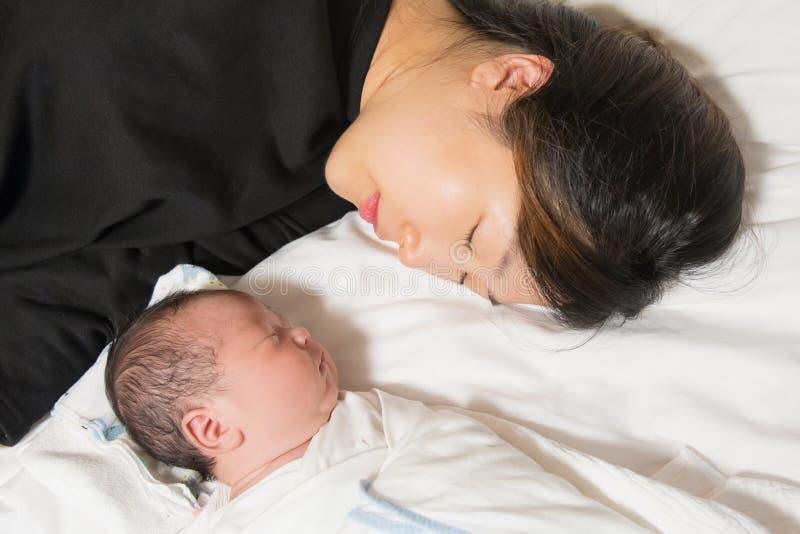 Giovane madre asiatica e suo il neonato che dormono pacificamente sul suo letto fotografia stock libera da diritti