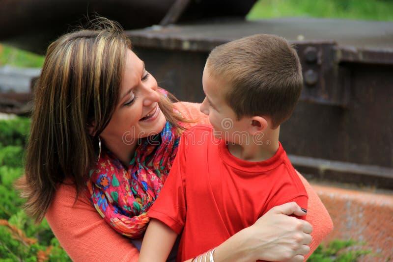 Giovane madre castana che tiene suo figlio nel rivestimento fotografia stock libera da diritti