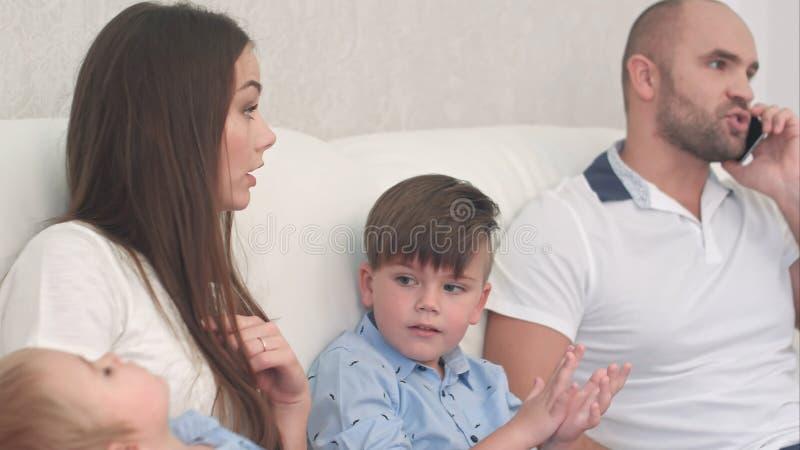 Giovane madre che è arrabbiata con il suo marito che parla sul telefono e che non gioca con i suoi figli fotografie stock libere da diritti