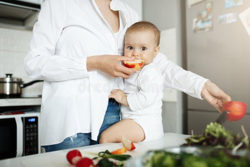 Giovane madre che alimenta il suo piccolo bambino con la mela mentre cucinando pranzo per la famiglia Bambino che si siede sulla  fotografie stock