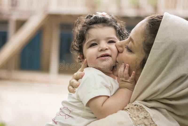 Giovane madre che bacia il suoi amore del bambino della bambina e Ca parenting fotografia stock