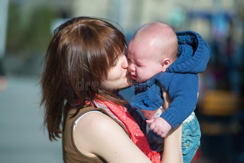Giovane madre che calma il suo bambino gridante fotografia stock libera da diritti