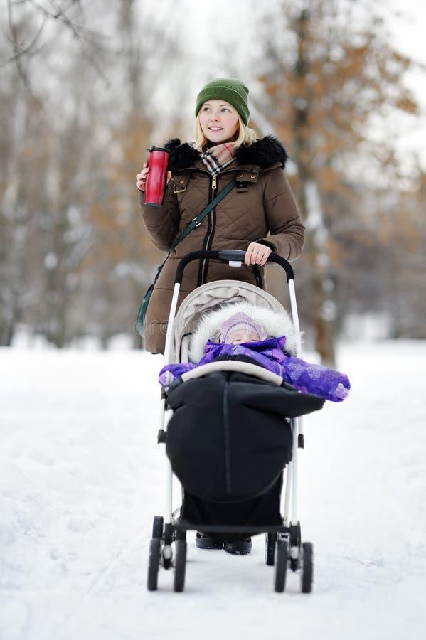 Giovane madre che cammina con il bambino in passeggiatore nell'inverno immagine stock