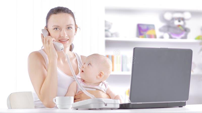 Giovane madre che comunica sul telefono Il concetto di freelancing immagini stock