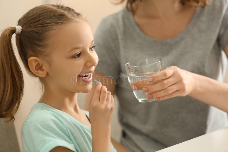 Giovane madre che dà pillola a sua figlia, all'interno immagini stock libere da diritti