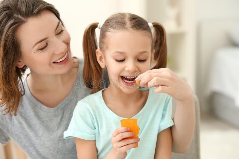 Giovane madre che dà pillola a sua figlia a casa immagine stock libera da diritti