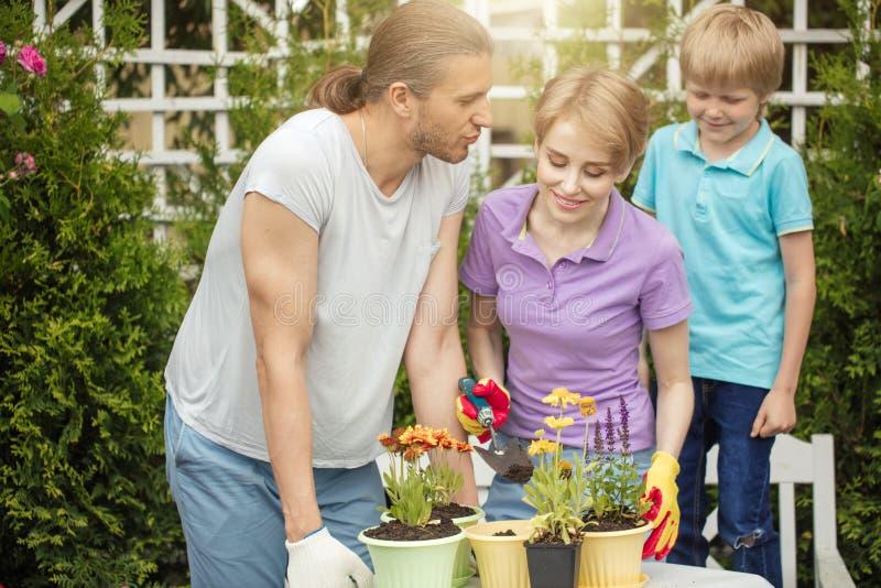 Giovane madre che fa il giardinaggio nel cortile posteriore anteriore o con i suoi due piccoli bambini svegli fotografie stock