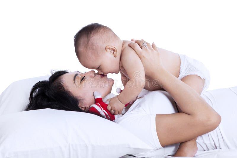 Giovane madre che gioca con il suo bambino isolato fotografia stock libera da diritti