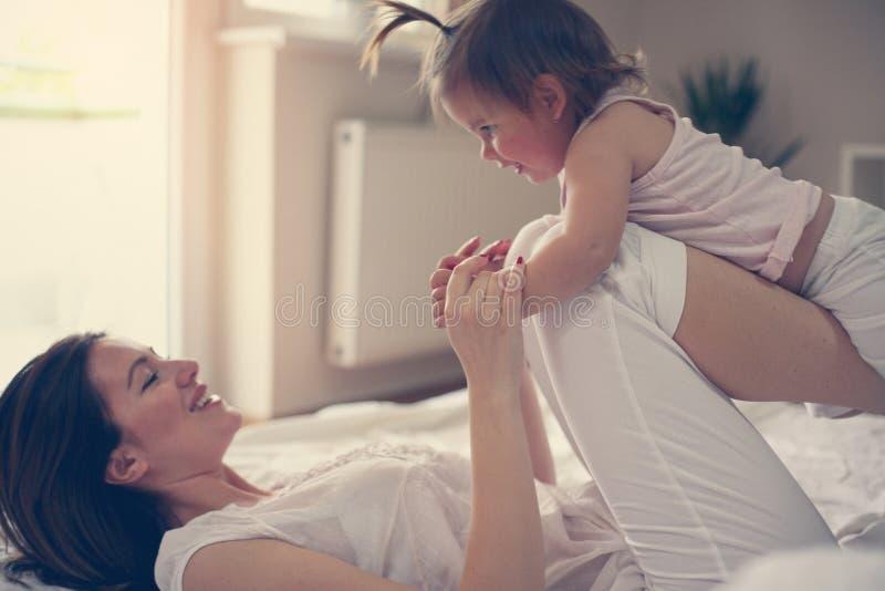 Giovane madre che gioca con la sua neonata a letto Godere della madre immagine stock