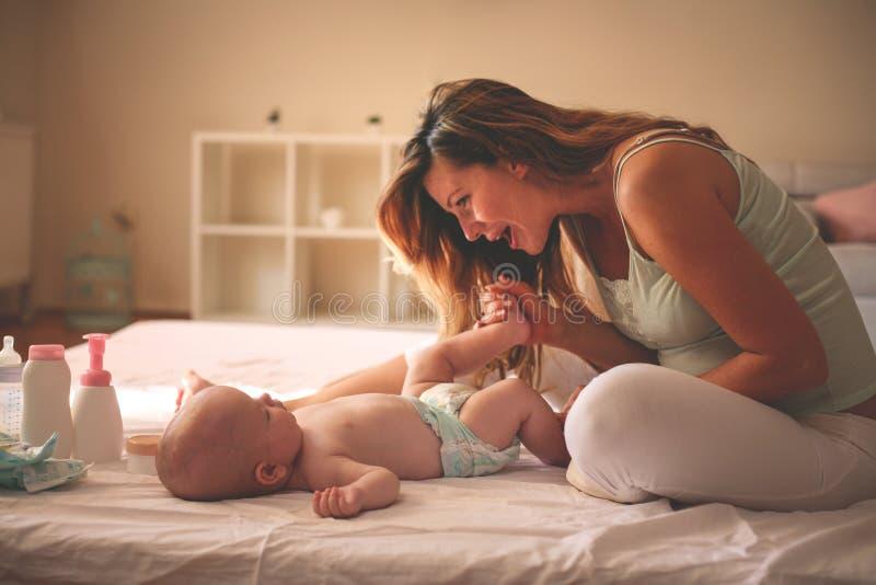 Giovane madre che gioca con la sua neonata a letto Godere della madre fotografia stock libera da diritti