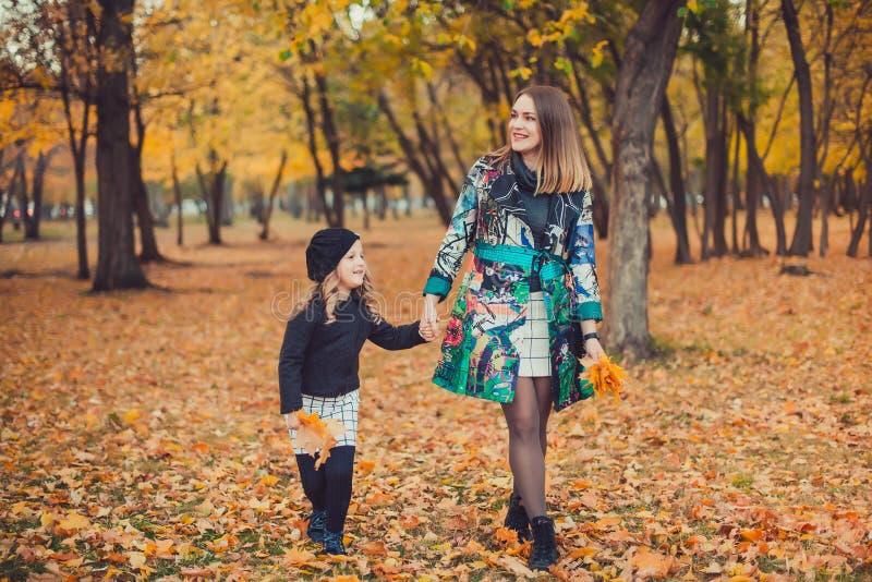 Giovane madre che gioca con sua figlia nel parco di autunno fotografia stock