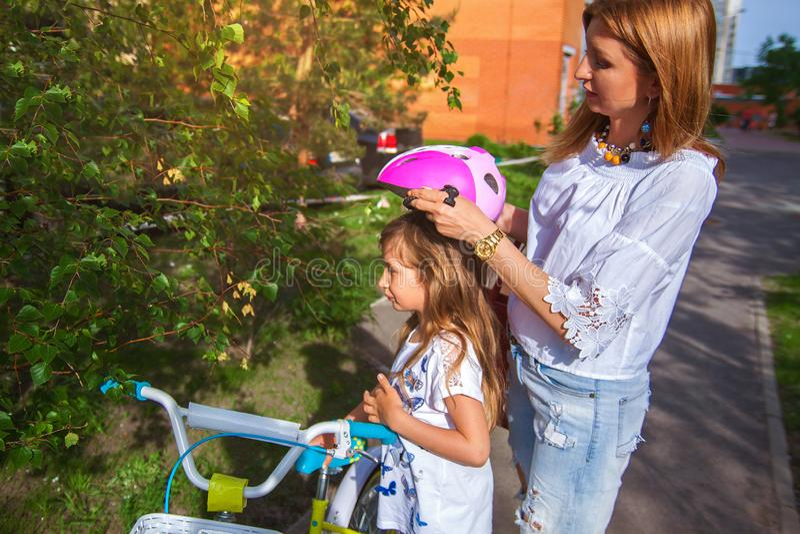 Giovane madre che insegna a sua figlia a come guidare una bicicletta nel parco immagine stock