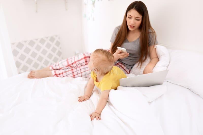 Giovane madre con il bambino che lavora al letto a casa fotografie stock libere da diritti
