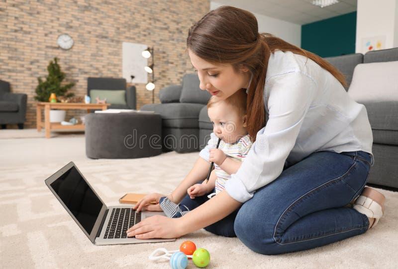 Giovane madre con il bambino che lavora al tappeto a casa immagini stock