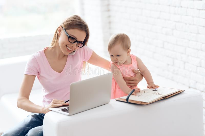 Giovane madre con il bambino che lavora e che per mezzo del computer portatile fotografia stock libera da diritti