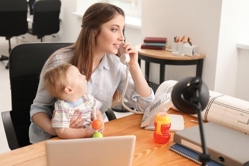 Giovane madre con il bambino che parla sul telefono mentre lavorando nell'ufficio immagine stock libera da diritti