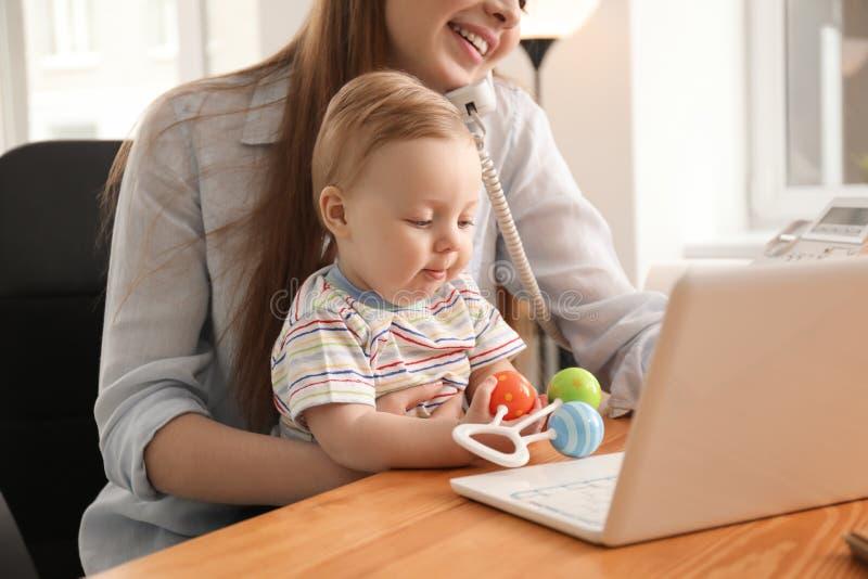 Giovane madre con il bambino che parla sul telefono mentre lavorando nell'ufficio fotografia stock