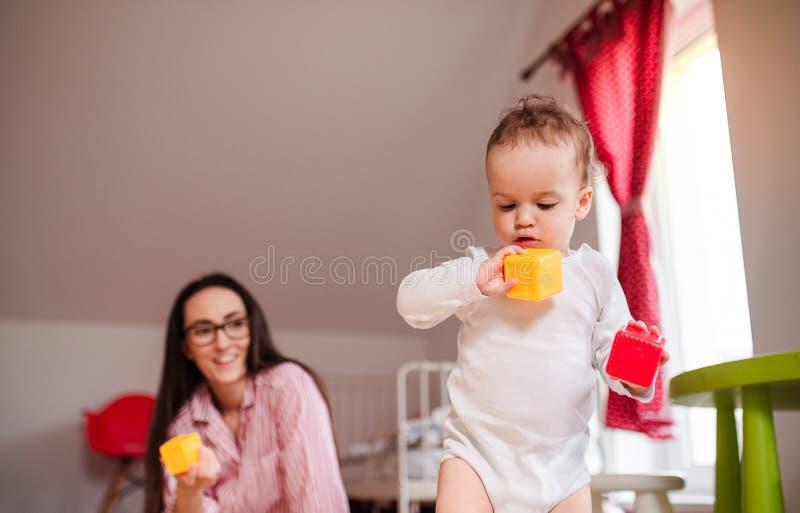 Giovane madre con il piccolo figlio del bambino all'interno a casa, giocando fotografie stock libere da diritti