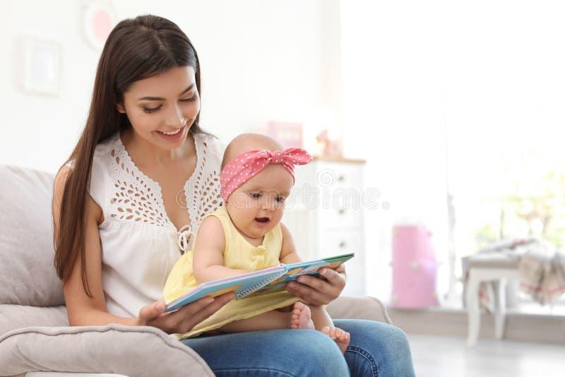 Giovane madre con il suo libro di lettura sveglio della neonata fotografie stock libere da diritti
