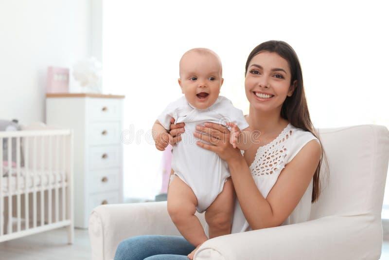 Giovane madre con la sua neonata sveglia in poltrona immagine stock libera da diritti