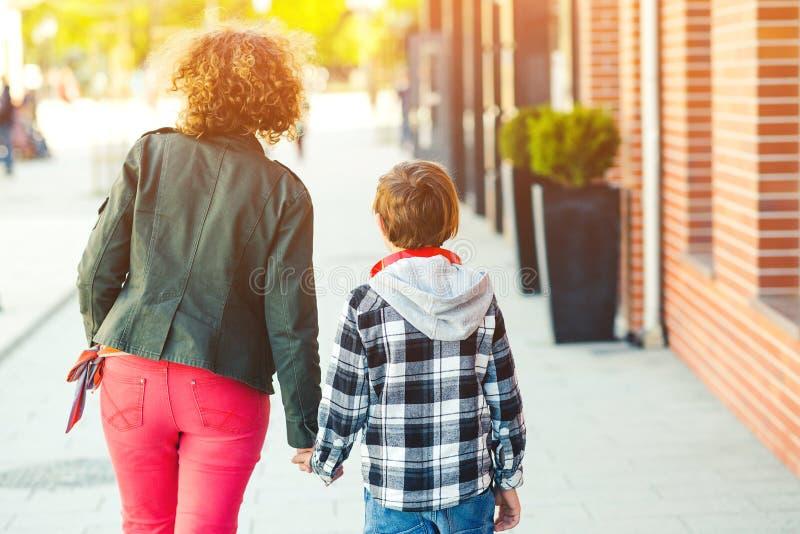 Giovane madre con un bambino che cammina in città e tiene la mano La donna e il figlio Concetto di fiducia familiare La mamma e i fotografie stock libere da diritti
