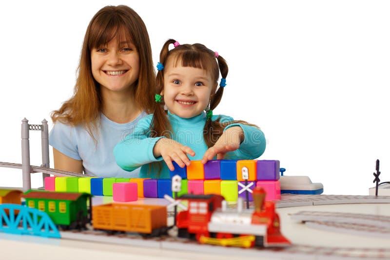 Giovane madre e figlia che giocano con i giocattoli fotografie stock