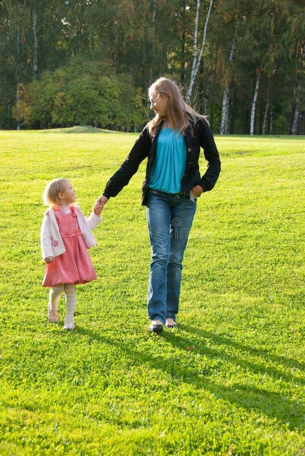 Giovane madre e figlia che giocano nella sosta fotografia stock