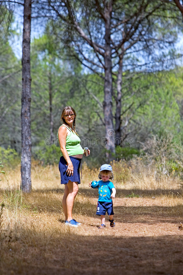 Giovane madre e figlio che camminano attraverso il legno fotografie stock