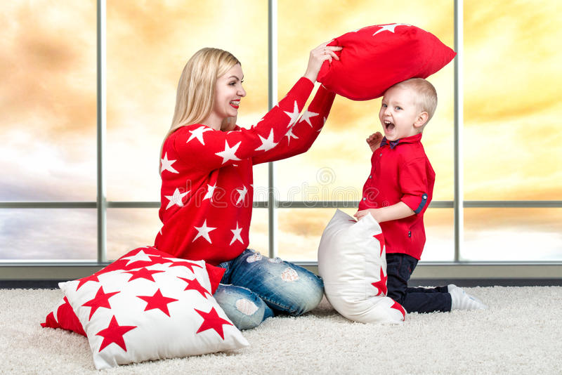 Giovane madre e piccolo figlio che giocano con i cuscini, lotta di cuscino Il concetto di una festa della famiglia Bei cuscini pe immagine stock
