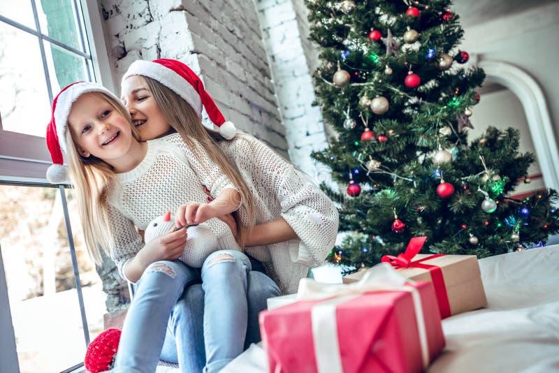 Giovane madre e ragazza sveglia divertendosi sulla notte di Natale in salone fotografia stock
