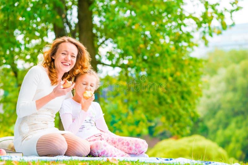 Giovane madre e sua la figlia che mangiano le mele fotografia stock libera da diritti