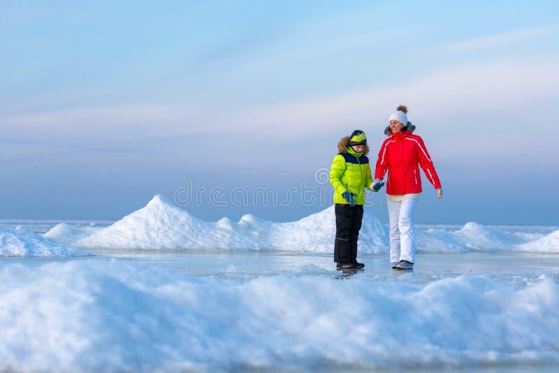 Giovane madre ed suo figlio sulla spiaggia ghiacciata immagini stock libere da diritti