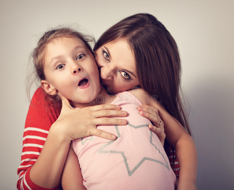 Giovane madre emozionale arrabbiata che vuole mordere il suo caprici impertinente fotografia stock libera da diritti